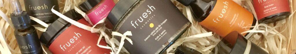 Fruesh Cosmetics produkter ligger i en låda med träspån.