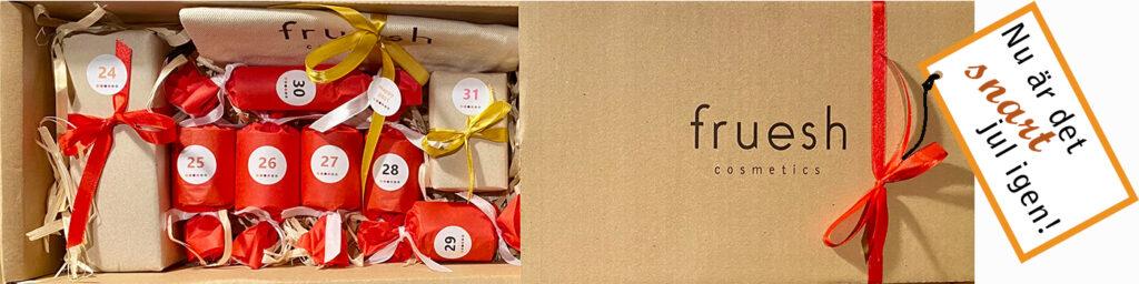 Frueshs apelsinprodukter på en bädd av träspån med apelsiner, kanel och en tygnecessär med en extra present i.