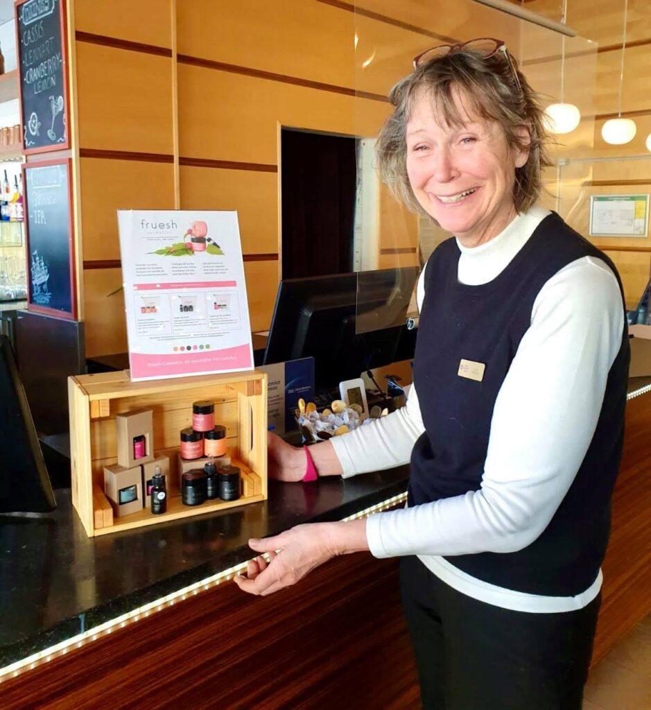 Ulla på Grand Hotel Elektra visar Frueshs produkter som står på receptionsdisken.