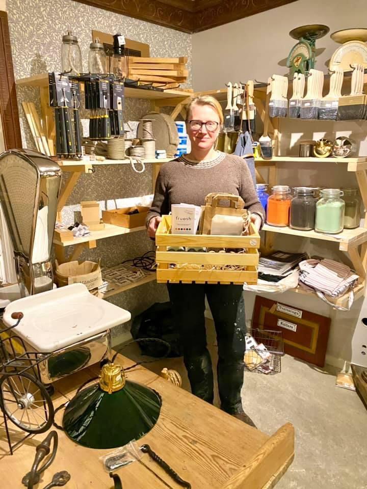 Åsa på Hantverkstan håller i lådan som Frueshs produkter levererades i.